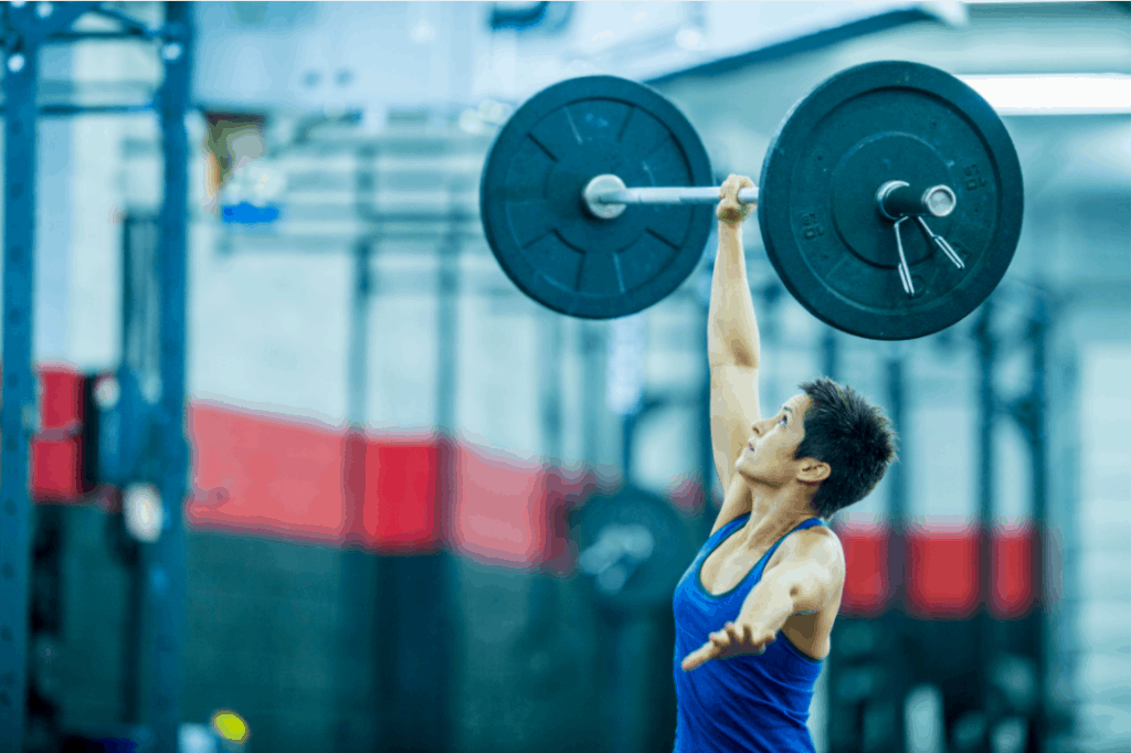Woman single handed snatch to highlight is powerlifting good for mma